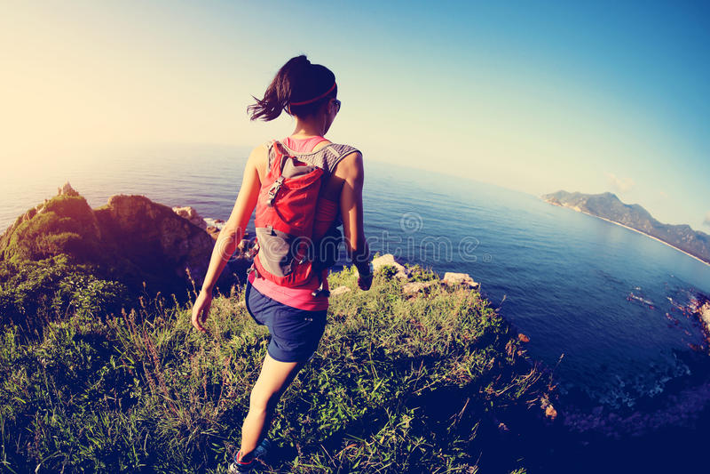 跑在海边山行迹的健身妇女 库存图片