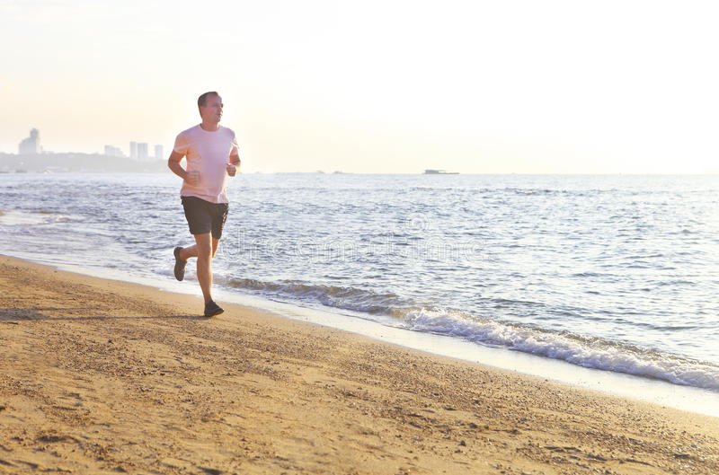 跑在海滩的人在surise 免版税库存照片
