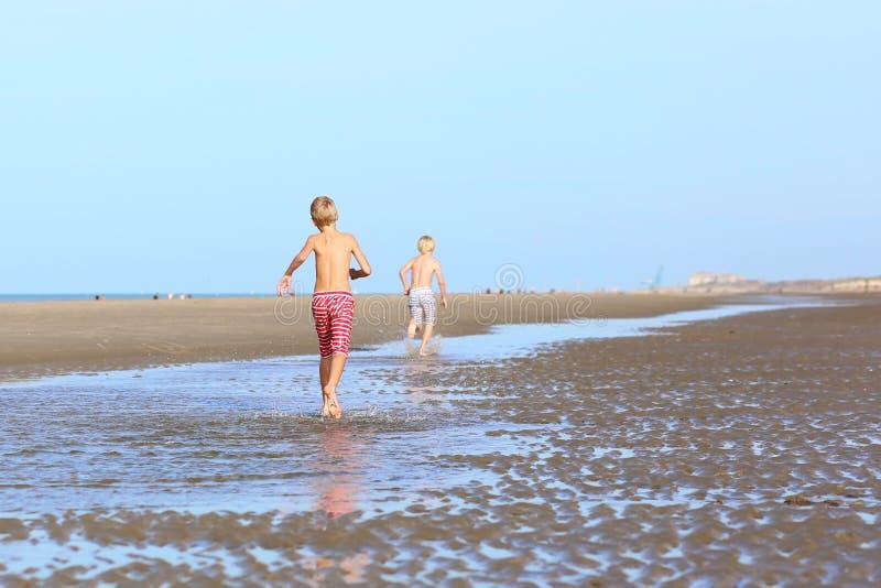 跑在海滩的双胞胎 库存照片