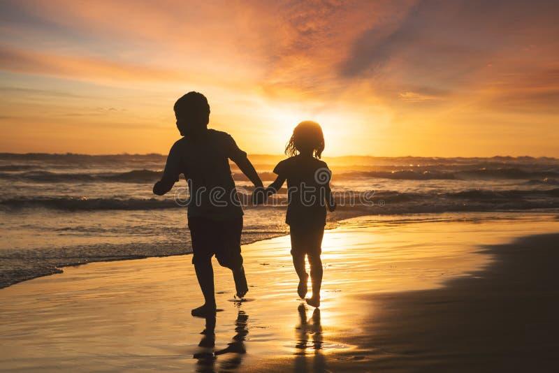 跑在海滩的快乐的孩子 免版税库存照片