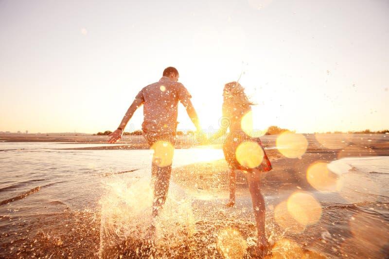 跑在海滩的夫妇 免版税库存照片