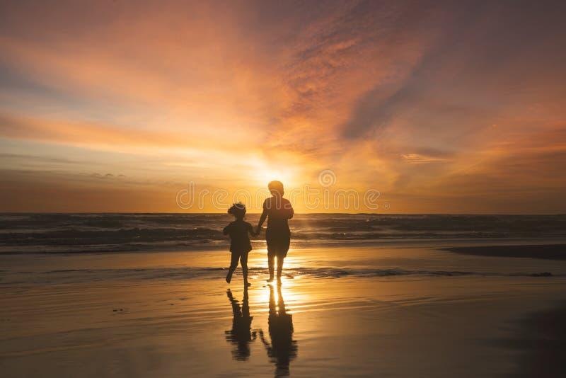 跑在海滩的愉快的孩子在日落时间 免版税库存图片