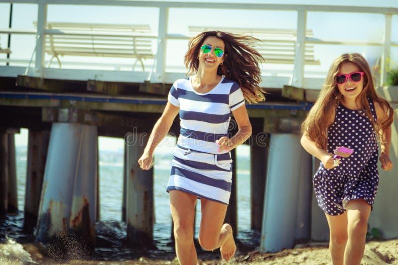 跑在海滩的愉快的无忧无虑的家庭海上 免版税库存照片