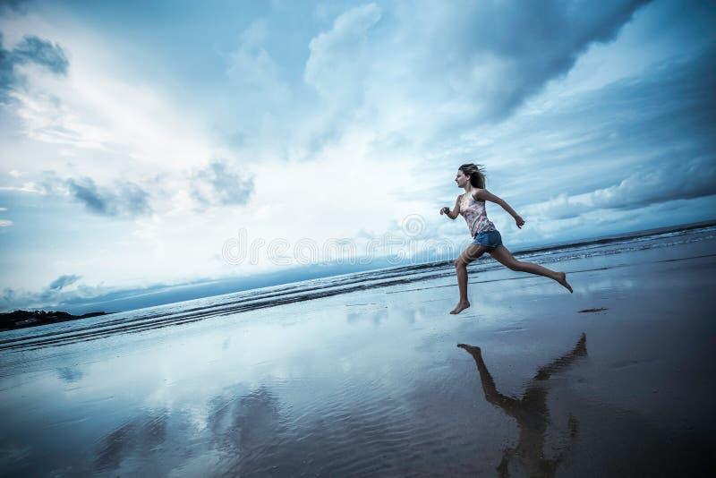 跑在海滩的美丽的运动的女孩 库存照片