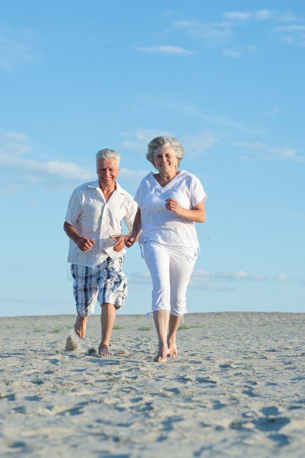 跑在海滩的老夫妇 免版税库存照片
