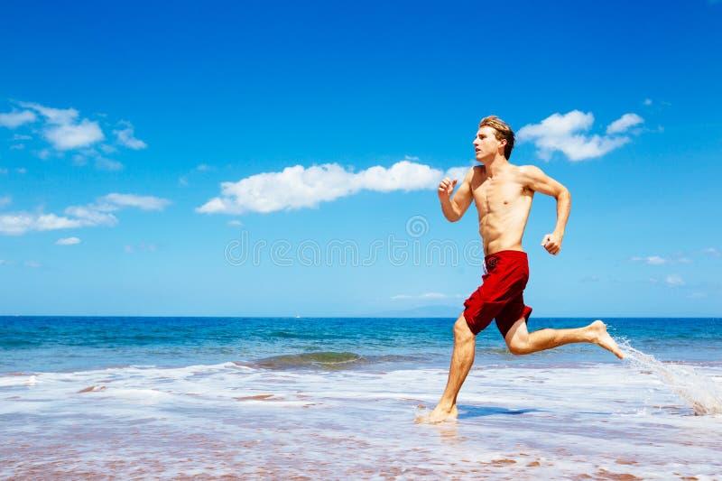 跑在海滩的运动人 库存照片