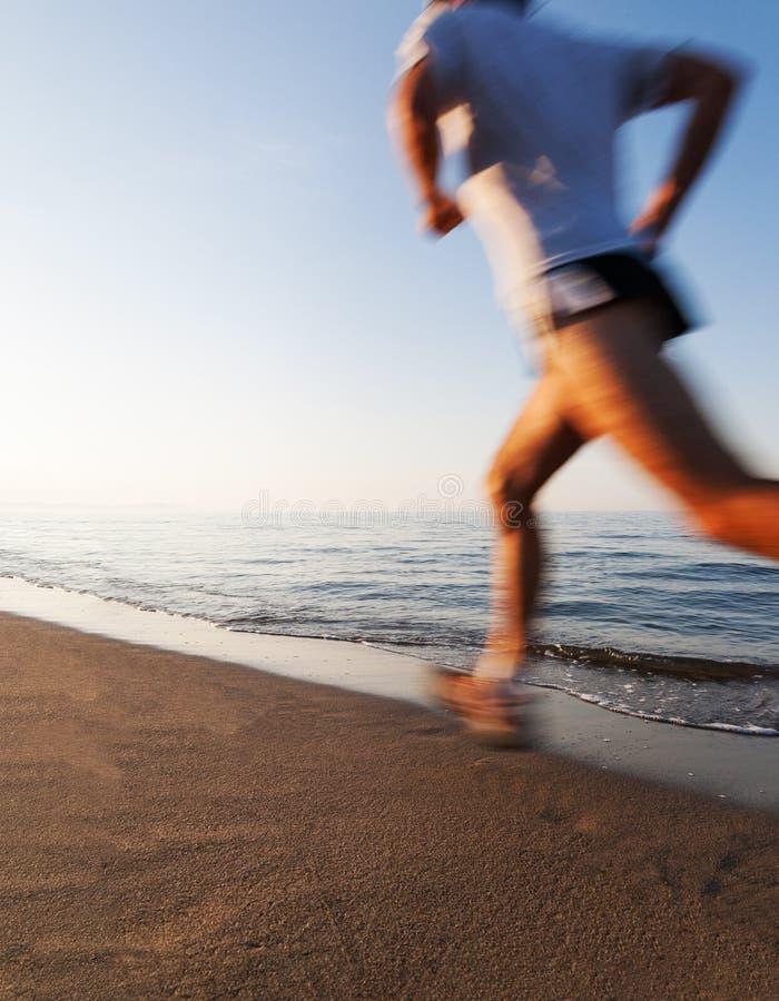跑在海滩的年轻人在日出 行动迷离作用 免版税库存照片