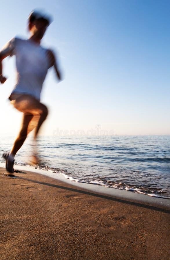 跑在海滩的年轻人在日出 行动迷离作用 免版税库存图片