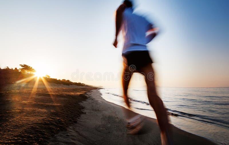 跑在海滩的年轻人在日出 行动迷离作用 库存照片