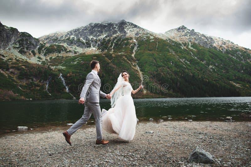跑在湖附近的婚姻的夫妇在太脱拉山在波兰 Morskie Oko 美好的夏日 免版税库存图片