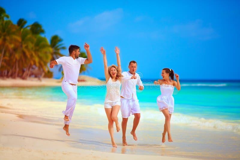 跑在热带海滩的小组愉快的朋友,暑假 免版税图库摄影