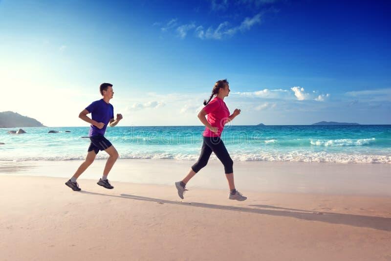 跑在热带海滩的男人和妇女 库存照片