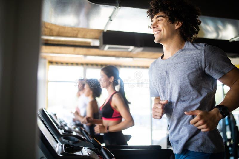 跑在现代体育健身房的踏车的小组青年人 库存照片