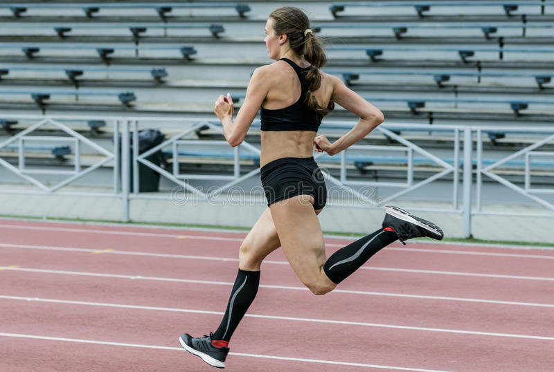 跑在田径运动体育场的少妇 免版税库存图片