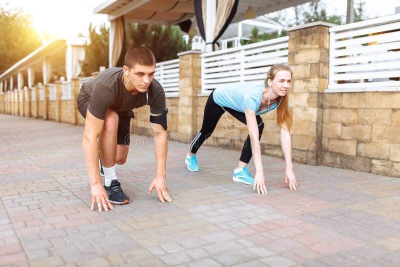 跑在男人和妇女的早晨,训练在工作前,两位人运动员 免版税库存照片