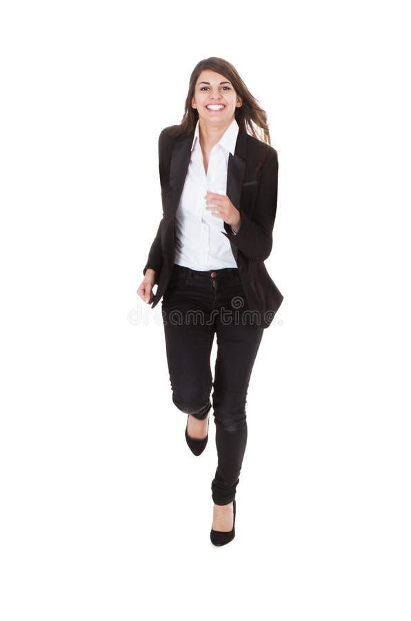 跑在白色背景的愉快的女实业家 图库摄影