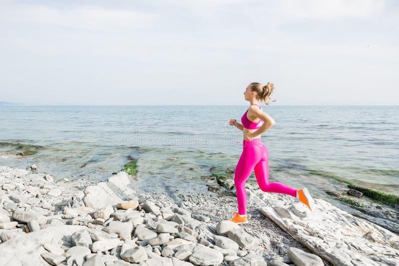 跑在石头的年轻可爱的健身女孩靠岸 库存图片
