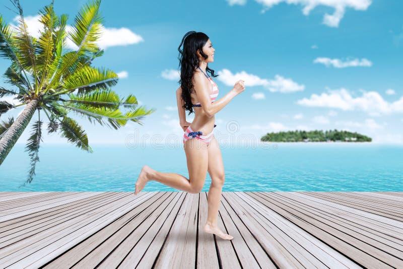 跑在码头的愉快的妇女 库存图片