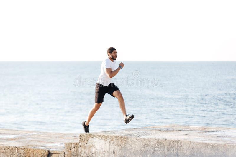 跑在码头的英俊的非洲运动员 免版税库存图片