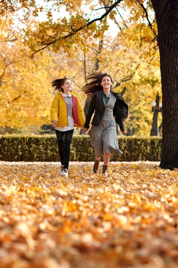 跑在秋天城市公园的两个愉快的女孩 库存照片