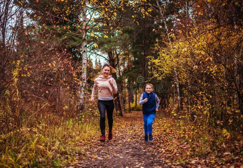 跑在秋天森林里的小男孩和他的姐妹 免版税库存图片