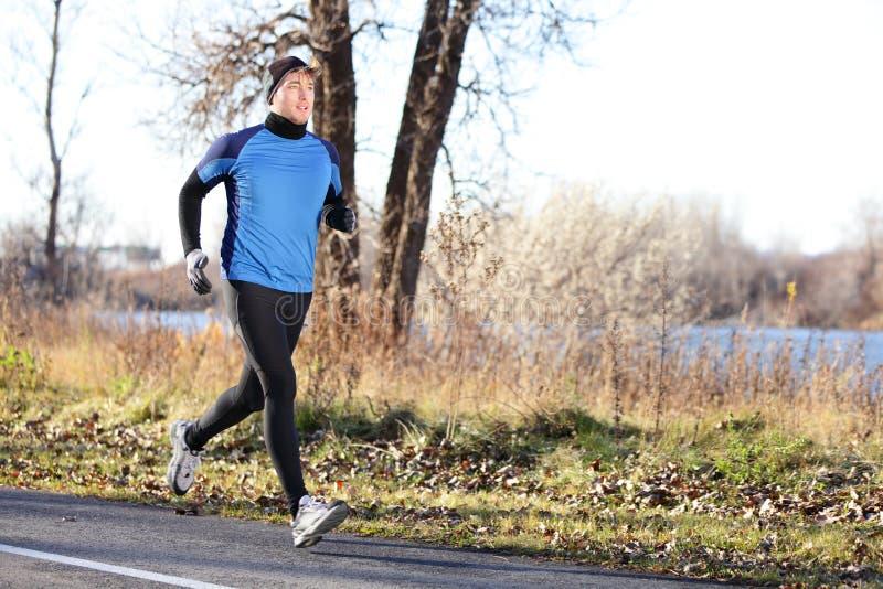 跑在秋天的男性赛跑者人在冷的天 免版税库存照片
