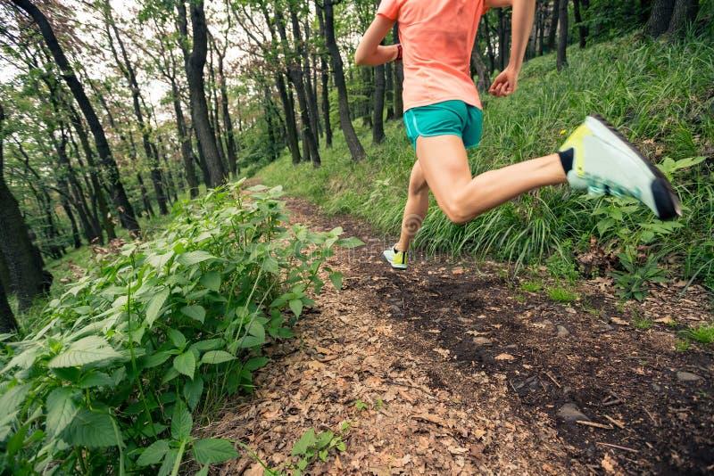 跑在绿色森林耐力体育的妇女足迹 免版税库存照片