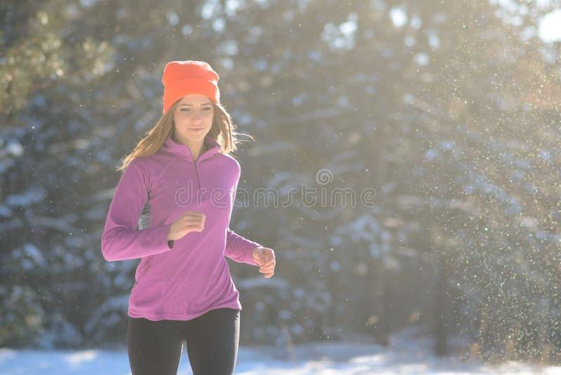 跑在美丽的冬天森林里的少妇在晴朗的冷淡的天 有效的生活方式概念 免版税库存照片