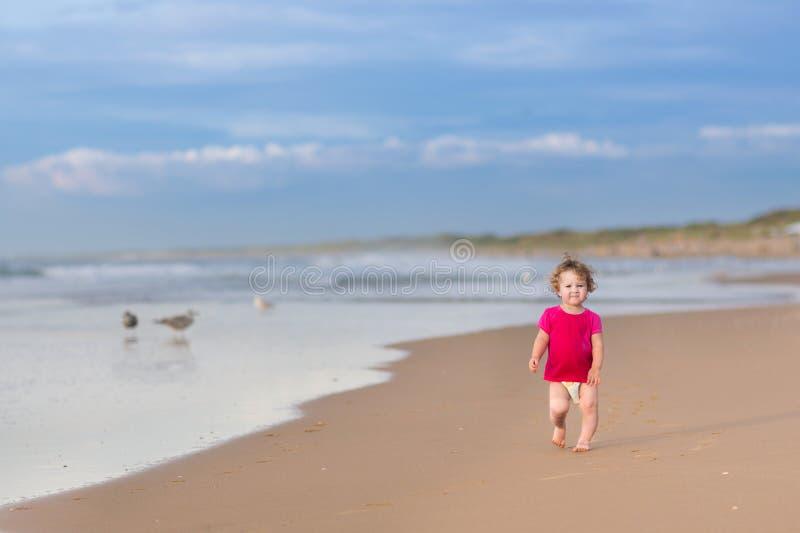 跑在美丽的海滩的逗人喜爱的滑稽的女婴 图库摄影