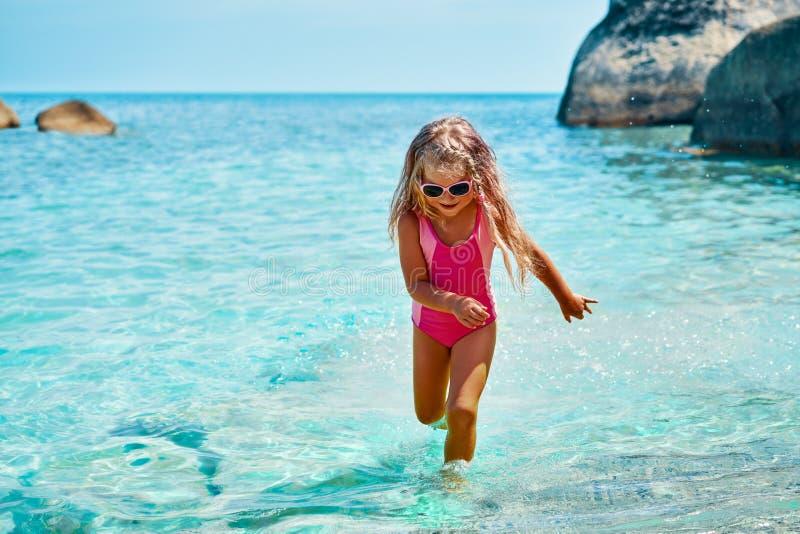 跑在美丽的热带海滩的绿松石海的逗人喜爱的女孩 库存照片