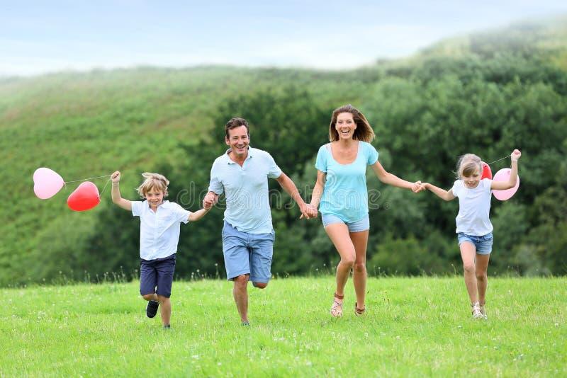 跑在美好的风景的快乐的家庭 免版税图库摄影