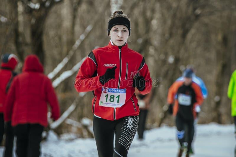 跑在胡同冬天公园下的美丽的女孩运动员 库存图片