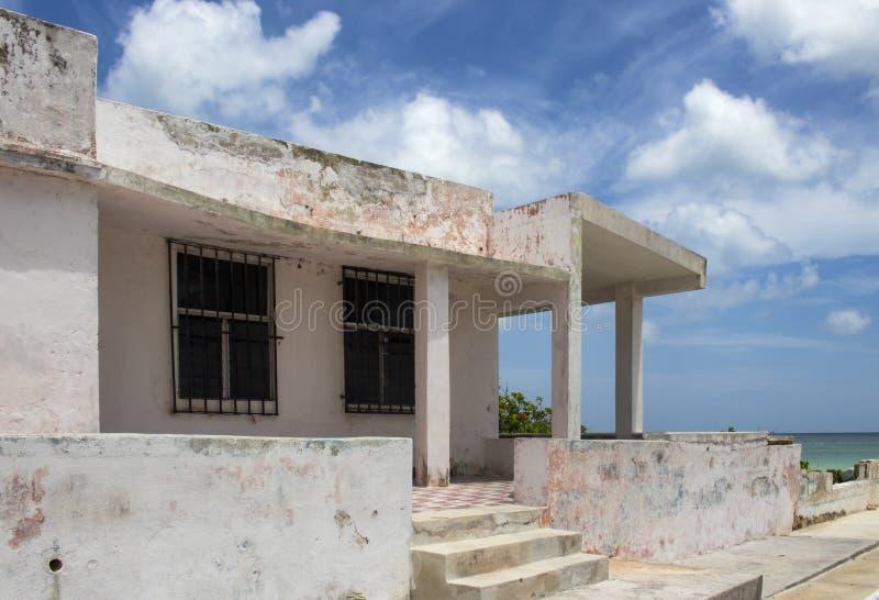 跑在脏的混凝土建筑下由防波堤在有海洋的墨西哥到一边和一块美好的蓝色多云天空天花板 图库摄影