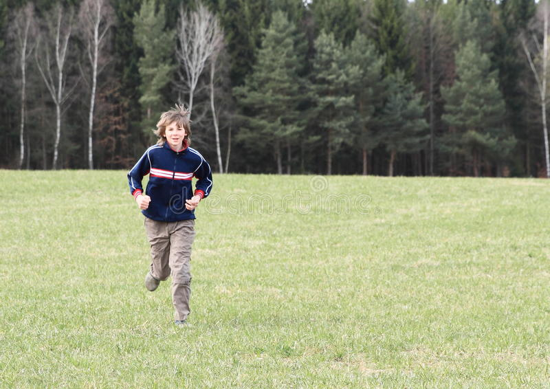 跑在草甸的男孩 免版税库存照片