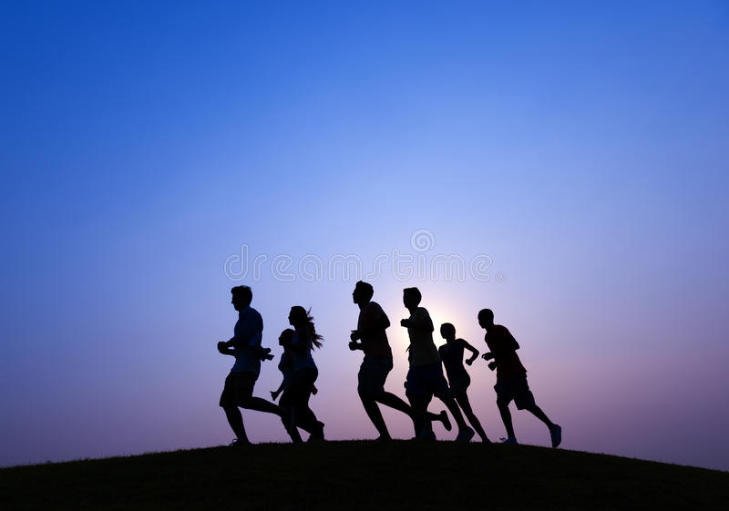 跑在蓝色日落的人们 免版税库存照片