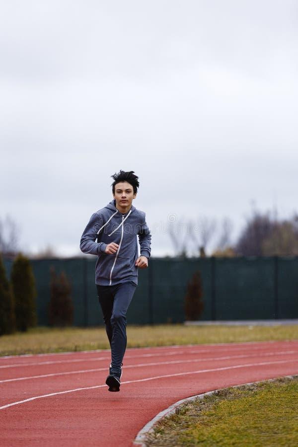 跑在跑马场的运动员亚裔年轻人在体育场内 免版税库存图片
