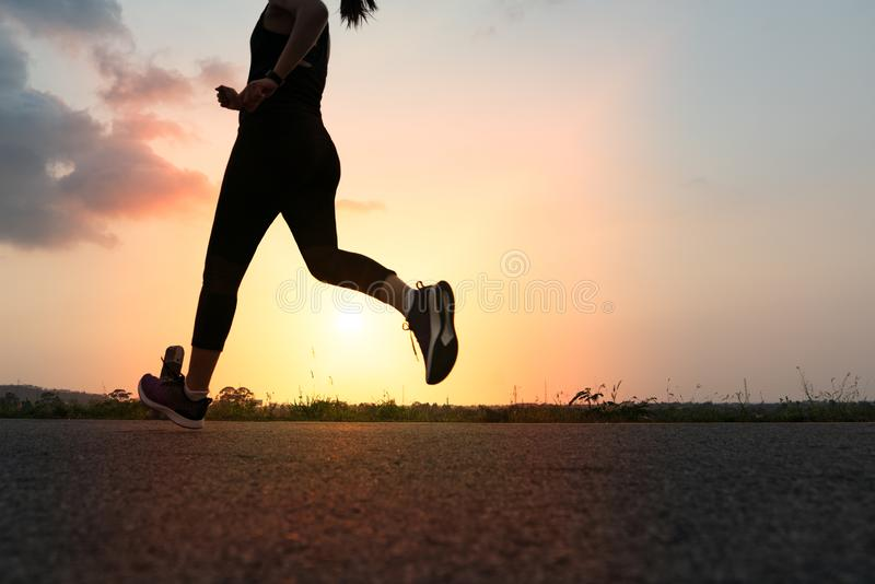 跑在路的体育妇女 健身在日落的妇女训练 免版税图库摄影