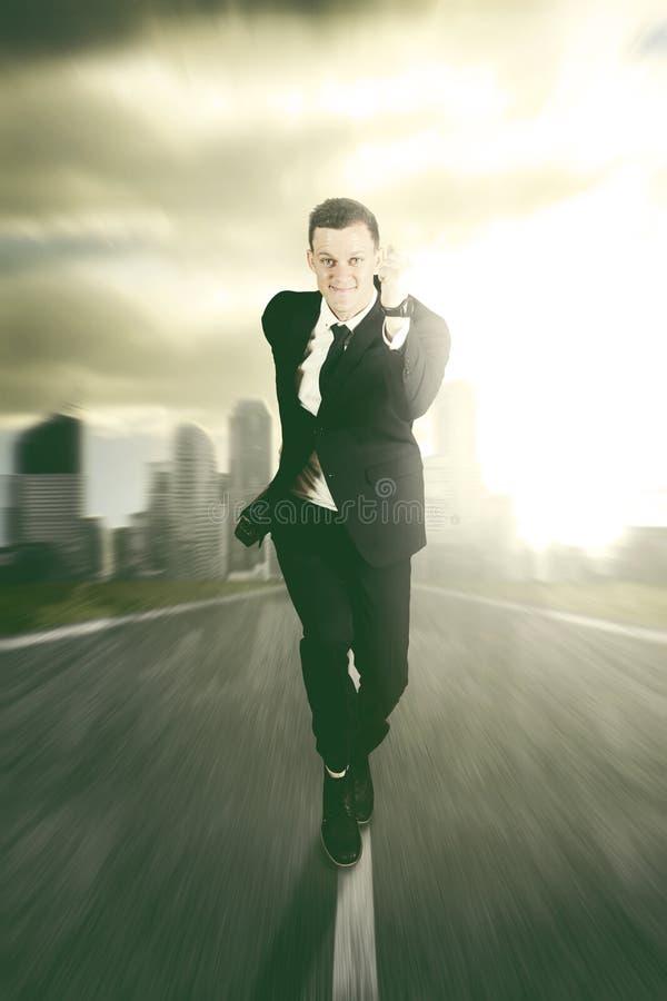 跑在路的商人反对都市风景背景 免版税库存照片