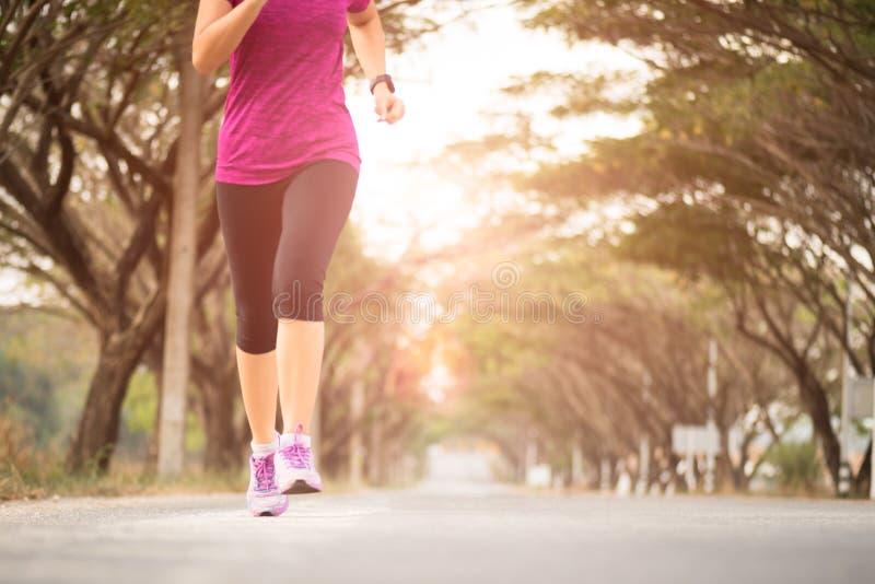 跑在路的年轻体育女孩赛跑者运动员软的焦点  体育和锻炼概念 免版税库存照片