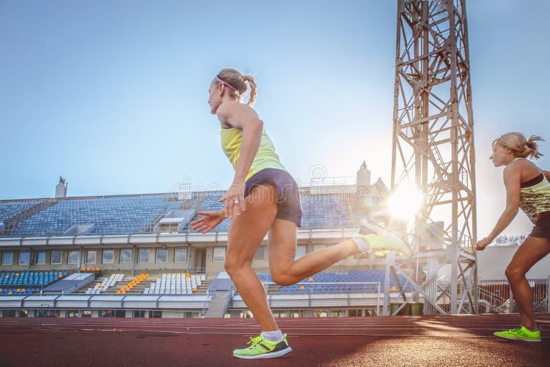 跑在踏车的两位女性短跑选手运动员赛跑在训练期间在竞技体育场内 库存照片