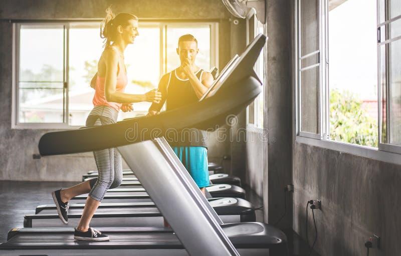 跑在踏车的体育亚裔妇女做心脏训练,发怒适合的身体和肌肉在健身房,被定调子的图象,后面看法 库存照片
