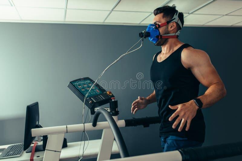 跑在踏车的健身人测试他的表现 免版税库存照片