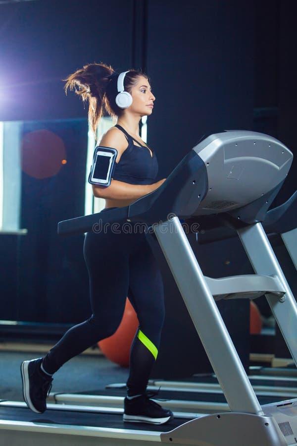 跑在踏车的年轻适合的妇女听到音乐通过耳机在健身房 概念健康生活方式 免版税图库摄影