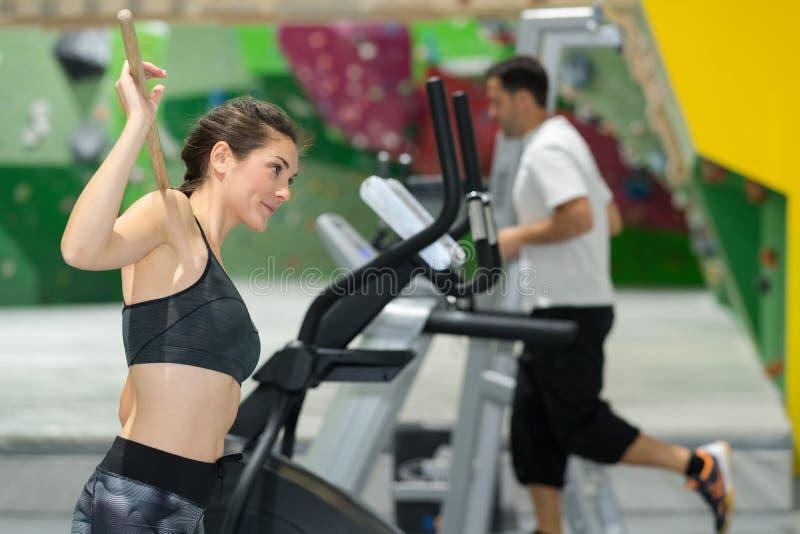 跑在踏车的运动的妇女在健身房 免版税库存图片