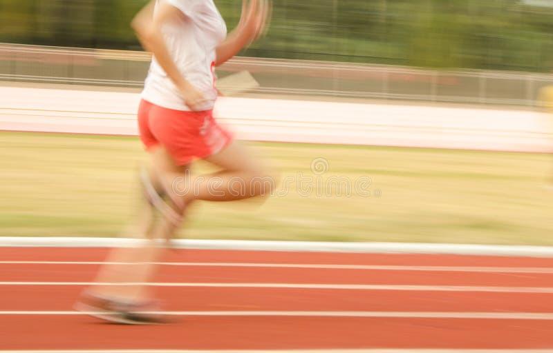 跑在轨道,模糊的运动的女运动员 图库摄影