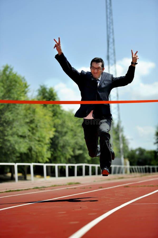 跑在运动轨道的商人庆祝在工作成功概念的胜利 库存图片