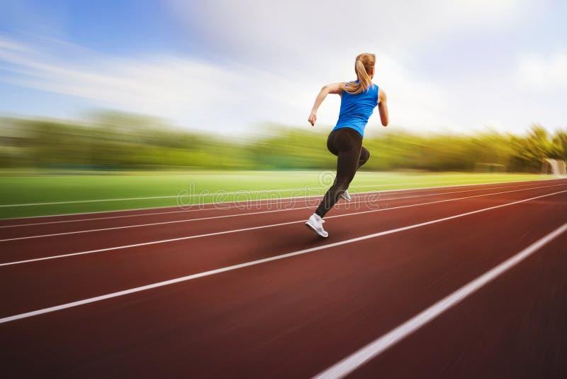 跑在迷离背景的连续轨道后面视图的美丽的年轻女运动员 运动员在体育场附近跑 库存照片