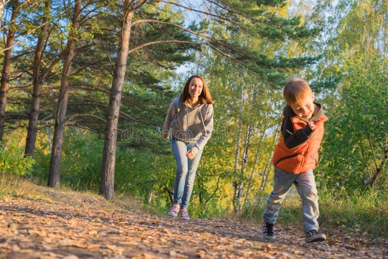 跑在道路的母亲和儿子在秋天森林里 免版税库存图片