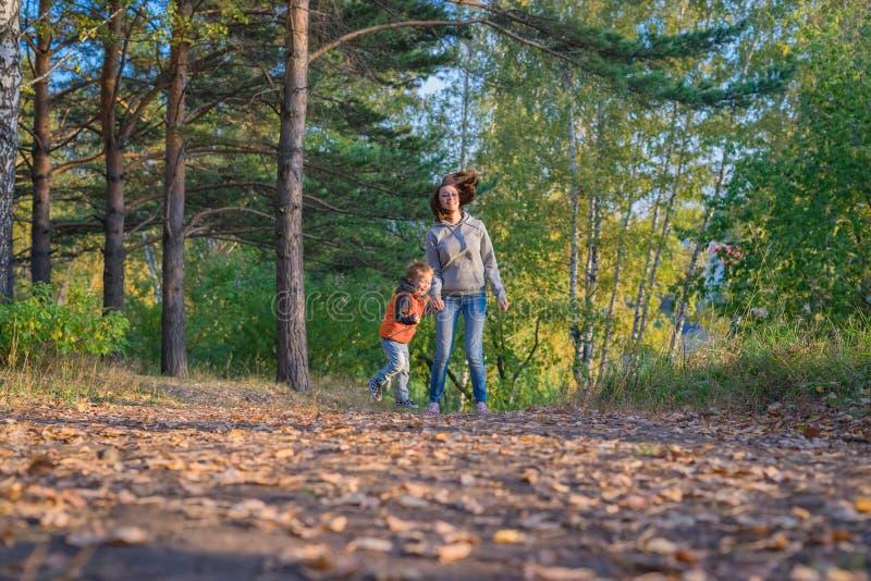 跑在道路的母亲和儿子在秋天森林里 免版税库存照片
