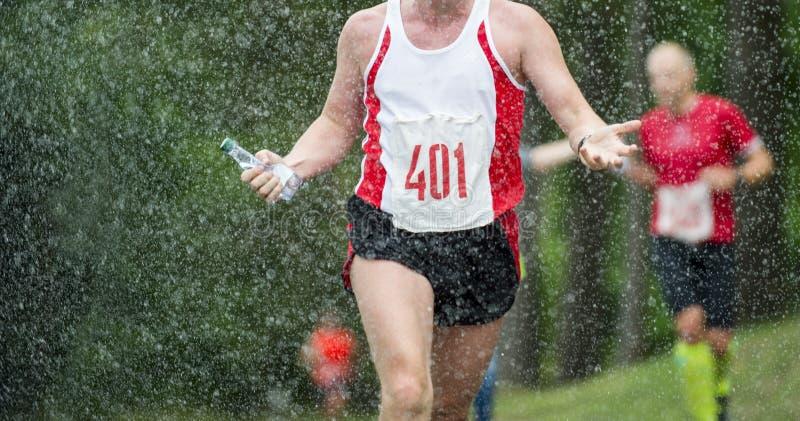 跑在雨下落城市马拉松下的赛跑者人 免版税库存照片
